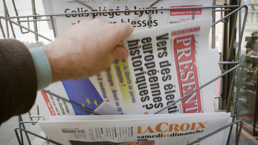buy newspaper : Strasbourg, France - May 25, 2019: Man hand POV reading at press kiosk Quotidien Present newspaper featuring 2019 European Parliament election predictions a day before the vote