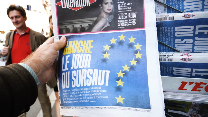 hot news : Strasbourg, France - May 25, 2019: Man hand POV reading at press kiosk newspaper featuring 2019 European Parliament election predictions a day before the vote Left wing a surprise title Stock Footage