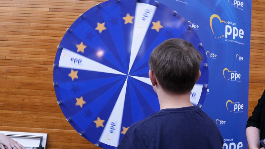 groupe : Strasbourg, France - Circa 2018: European Peoples Party exhibition stand lucky wheel roulette with young boy spinning and winning prize a pencil - European Parliament interior during open day Stock Footage