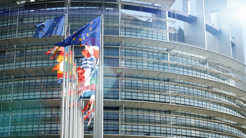 all european flags : Cinematic sunlight flare over European Parliament headquarter in Strasbourg with all European Union Flags waving in the wind in the Sunday of 2019 European Parliament election slow motion