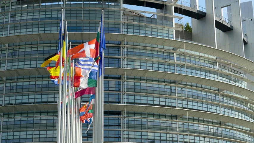společenství : European Parliament headquarter in Strasbourg with all European Union Flags waving in calm wind in the Sunday of 2019 European Parliament election - sunny clear day