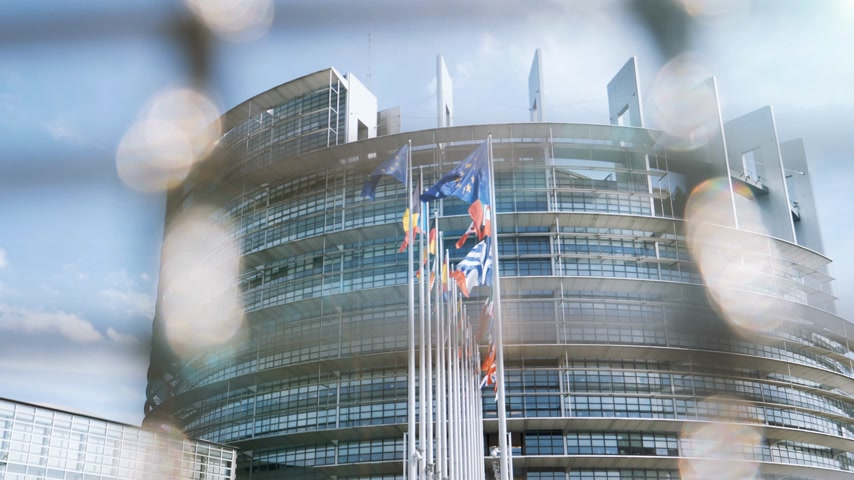 debata : European Parliament headquarter in Strasbourg view through security fence with all European Union Flags waving in the wind in the Sunday of 2019 European Parliament election
