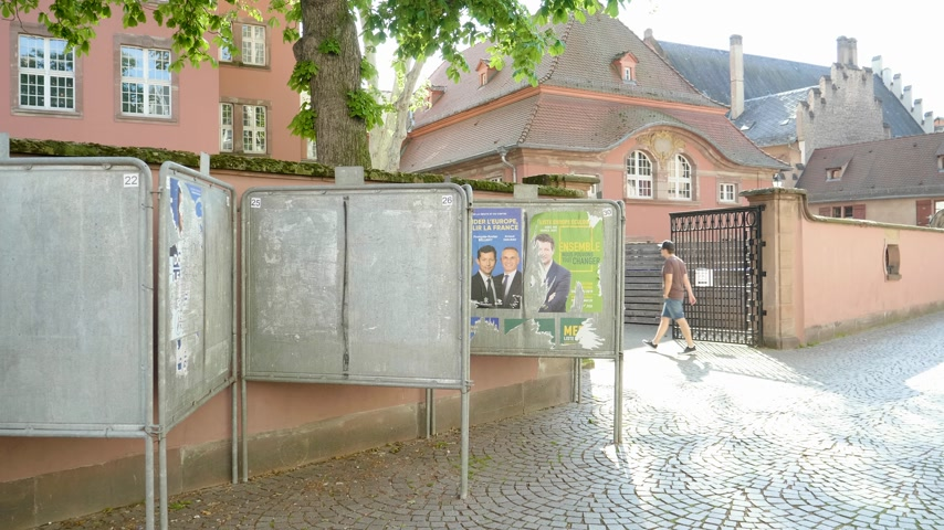 election campaign : Strasbourg, France - May 27, 2019: French school entrance with all candidates campaign posters to 2019 European Parliament election - man entering walking to polling station Bureau de vote Stock Footage
