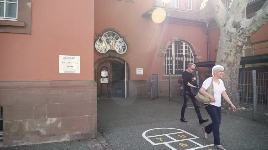 erledigt : Strasbourg, France - May 27, 2019: Slow motion people exits French polling station Bureau de vote door 26 May, Sunday of 2019 European Parliament election - cinematic sunlight flare