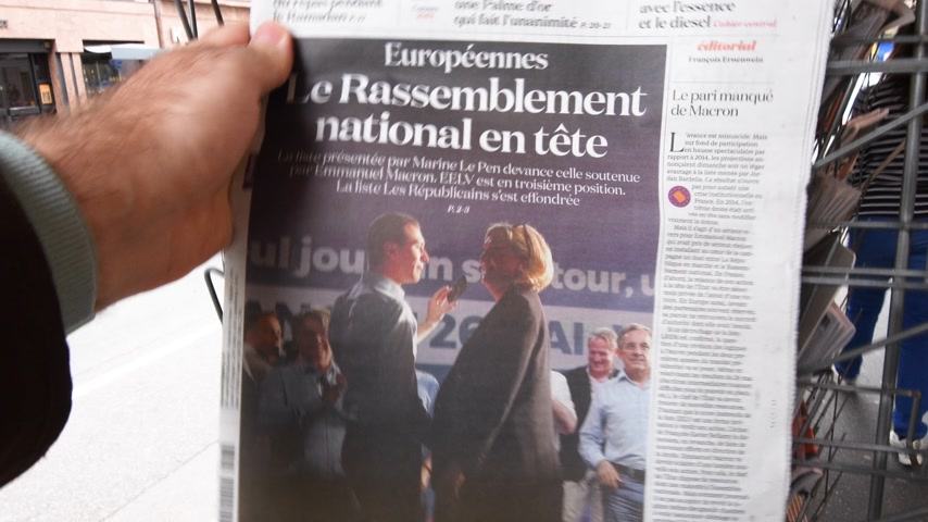 szemléltető : Strasbourg, France - May 27, 2019: Man holding buying La Croix newspaper front page on street press kiosk newsstand with the results of 2019 European Parliament election - Featuring Marine Le Pen and Jordan Bardella