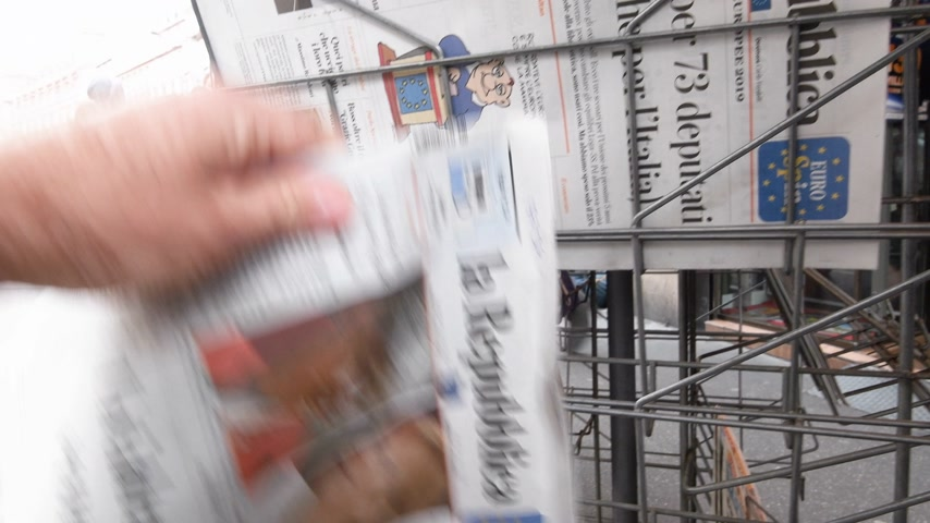 buy newspaper : Strasbourg, France - May 27, 2019: Man holding buying newspaper La Repubblica Italian press front page on street press kiosk newsstand with the picture of Theresa May and Angela Merkel