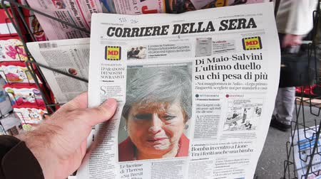 buy newspaper : Strasbourg, France - May 27, 2019: Man holding buying newspaper Corriere della sera front page on street press kiosk newsstand with the Theresa May crying announcing resignation Stock Footage
