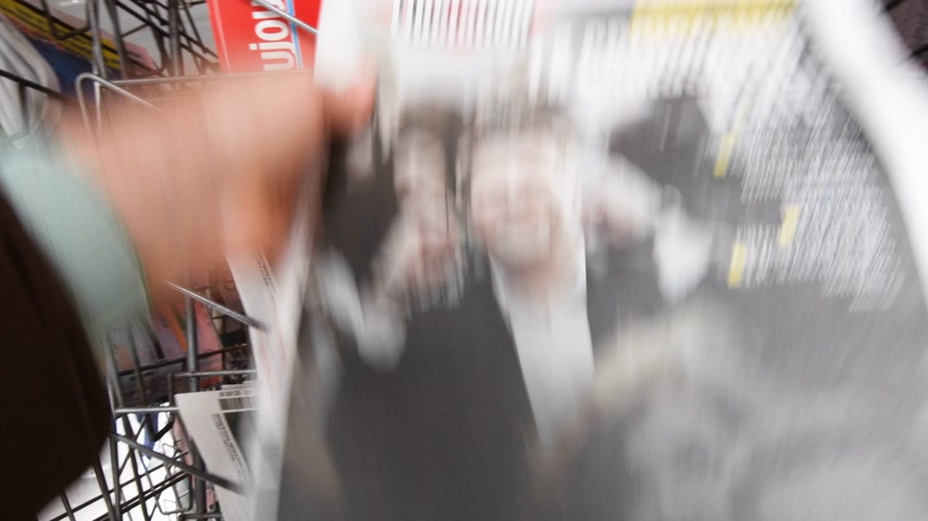 front cover : Strasbourg, France - May 27, 2019: Man holding buying Liberation newspaper front page with Yannick Jadot Green Party on street press kiosk newsstand with the results of 2019 European Parliament election