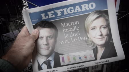 front cover : Strasbourg, France - May 27, 2019: Man holding buying Le Figaro newspaper front page on street press kiosk newsstand with the results of 2019 European Parliament election Emmanuel Macron and Le Pen on cover Stock Footage