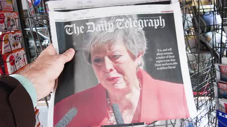 buy newspaper : Strasbourg, France - May 27, 2019: Man holding buying newspaper The Daily Telegraph front page on street press kiosk newsstand with the Theresa May crying announcing resignation Stock Footage