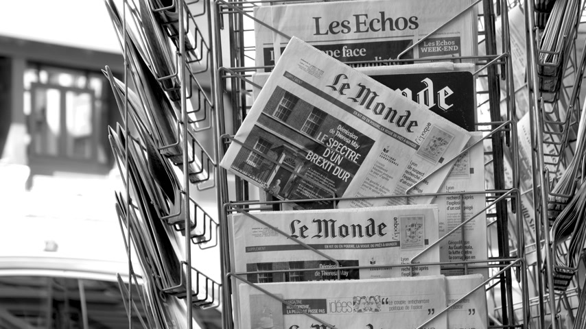 latest : Strasbourg, France - May 25, 2019: Silhouettes of pedestrians in front of multiple Le Monde press kiosk newspaper featuring Theresa May and title Spectre of a hard Brexit - black and white Stock Footage