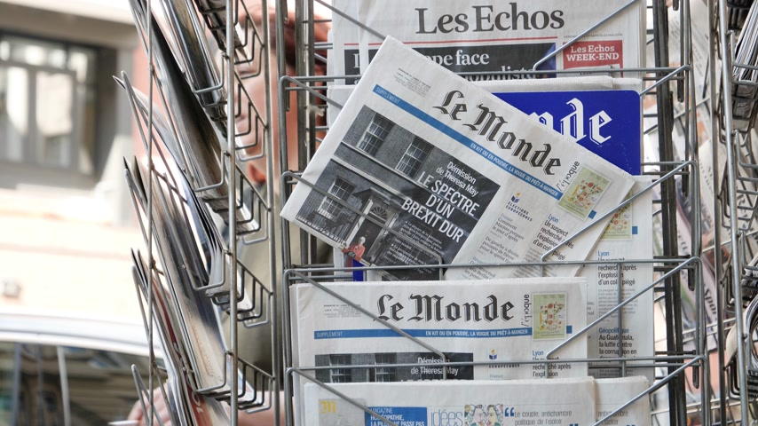 tabloid : Strasbourg, France - May 25, 2019: People pedestrians in front of multiple Le Monde press kiosk newspaper featuring Theresa May and title  specter of a hard Brexit - slow motion
