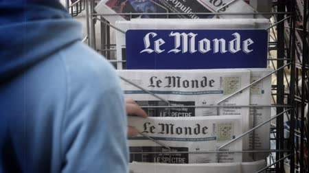 latest : Strasbourg, France - May 25, 2019: Adult French man buying Le Monde at press kiosk newspaper featuring Theresa May and title Spectre of a hard Brexit - slow motion VHS old tape film effect