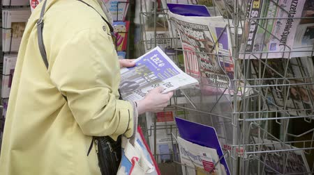 buy newspaper : Strasbourg, France - May 25, 2019: Slow motion Senior woman reading German TAZ newspaper at press kiosk featuring 2019 European Parliament election predictions a day before the vote Stock Footage