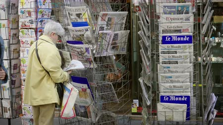buy newspaper : Strasbourg, France - May 25, 2019: Side view of senior woman buying multiple international newspaper at press kiosk featuring 2019 European Parliament election predictions a day before the vote