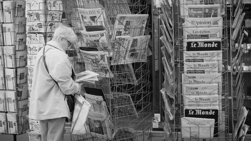 buy newspaper : Strasbourg, France - May 25, 2019: Side view of senior woman buying multiple international newspaper at press kiosk featuring 2019 European Parliament election predictions a day before the vote - black and white