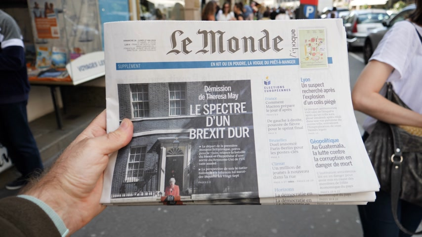 hot news : Strasbourg, France - May 25, 2019: Adult French man pov buying Le Monde at press kiosk newspaper featuring Theresa May and title Spectre of a hard Brexit - slow motion Stock Footage