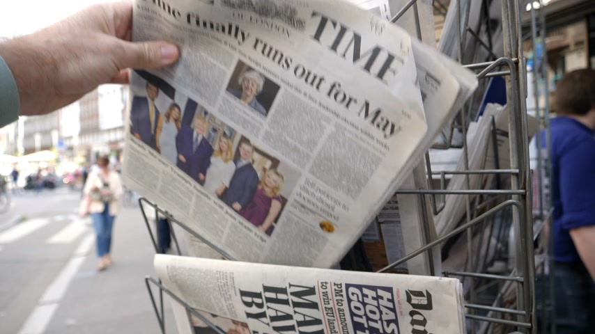 buy newspaper : Strasbourg, France - May 25, 2019: Man hand POV reading at press kiosk British The Times latest newspaper featuring Theresa May resignation slow motion city