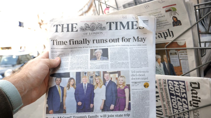 french media : Strasbourg, France - May 25, 2019: Man hand POV reading at press kiosk British The Times latest newspaper featuring Theresa May resignation slow motion city view in background