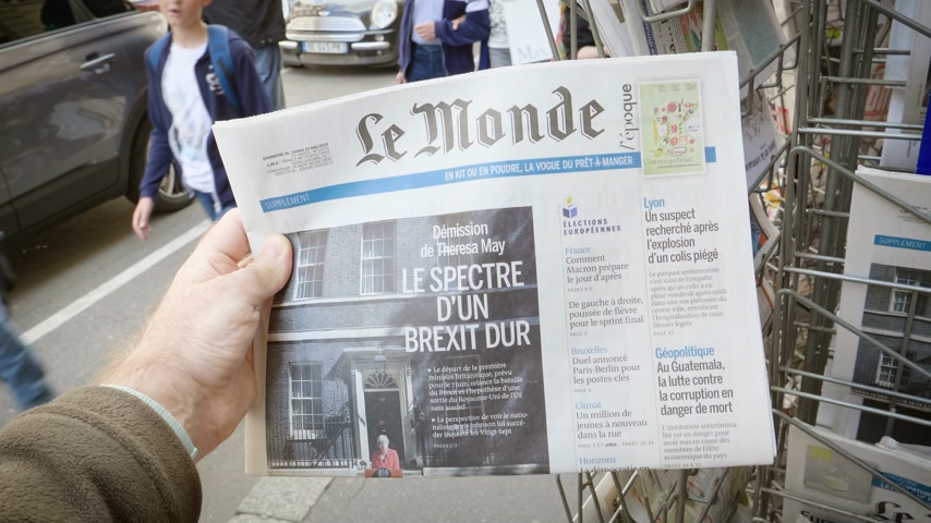 buy newspaper : Strasbourg, France - May 25, 2019: Adult French man buying Le Monde at press kiosk newspaper featuring Theresa May and title Spectre of a hard Brexit