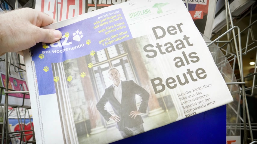 hot news : Strasbourg, France - May 25, 2019: Man hand POV reading TAZ at press kiosk newspaper featuring EU news and title der Staat als Beute Stock Footage