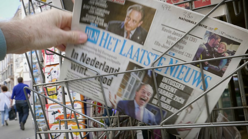 hot news : Strasbourg, France - May 25, 2019: Man hand POV reading at press kiosk Het Laatste Nieuws newspaper featuring Nigel Farage and Brexit news