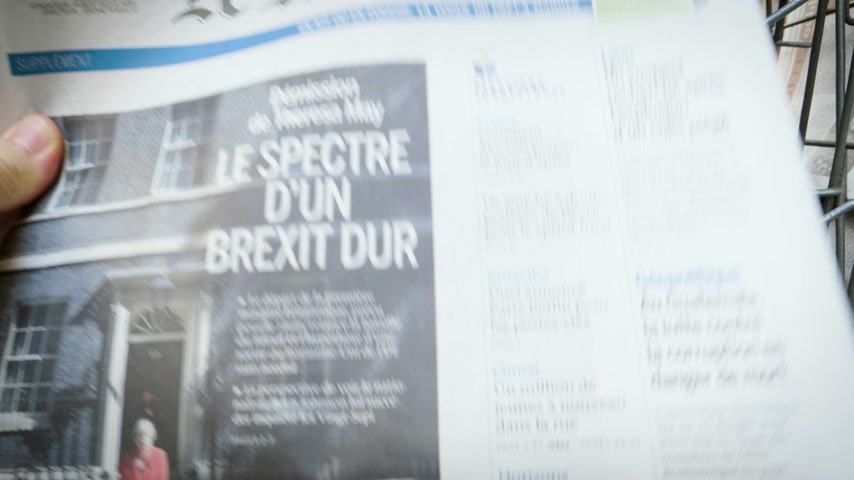 článek : Strasbourg, France - May 25, 2019: Adult French man buying Le Monde at press kiosk newspaper featuring Theresa May and title Spectre of a hard Brexit