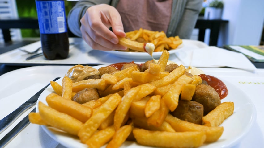 пюре : Close-up view woman eating delicious French fries and traditional Swedish meatballs Kottbullar
