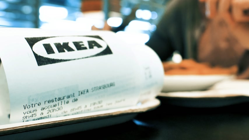 almôndega : Strasbourg, France - Circa 2019: Macro close-up of IKEA paper receipt as woman eats inside IKEA food restaurant French fries and Swedish meatballs drinking Pepsi sweet drink