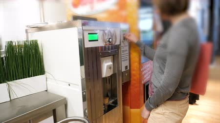 ikea : Paris, France - Circa 2019: Elegant woman inside IKEA food restaurant self-service waiting for the parlor ice-cream cone with twisted milk cream from machine problem with the money coin