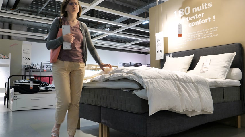 ikea : Paris, France - Circa 2019: Woman looking at bed duvet choosing furniture and bed linen mattress shopping for home bedroom renovation