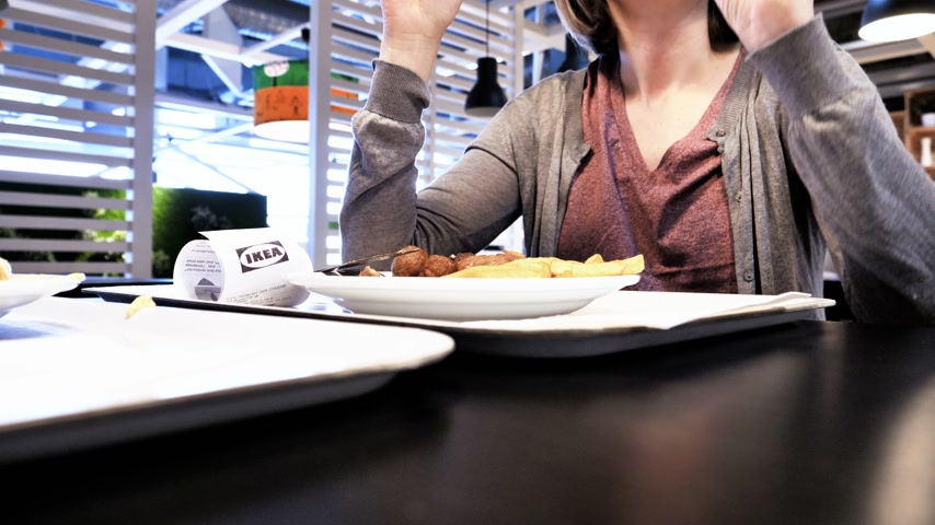 İsveççe : Paris, France - Circa 2019: Woman and man inside IKEA food restaurant eating French fries and Swedish meatballs drinking Pepsi sweet drink - woman reading components ingredients calories on the bottle Stok Video