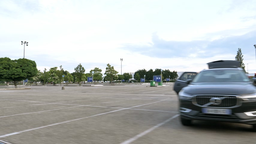 ikea : Strasbourg, France - Circa 2019: View of IKEA furniture store parking with woman loading inside Volvo XC90 SUV with trailer boxes of furniture Stock Footage