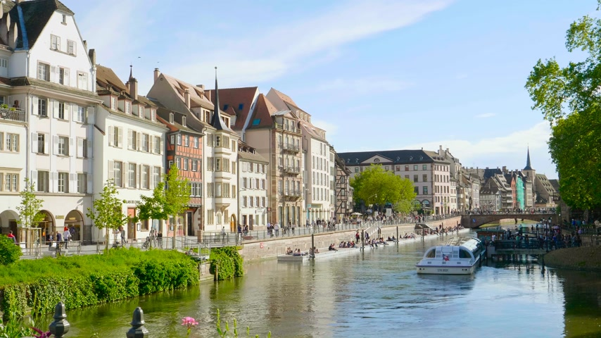 half timbered houses : Strasbourg, France - Circa 2019: Strasbourg famous promenade pedestrian street Quai des Bateliers with half timbered houses and people disembarking Batorama boat in port