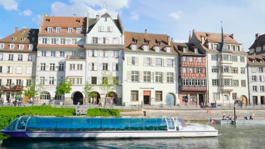 half timbered houses : Strasbourg, France - Circa 2019: Time lapse fast motion of Strasbourg famous promenade pedestrian street Quai des Bateliers with half timbered houses and people having fun admiring Batorama tourist boat