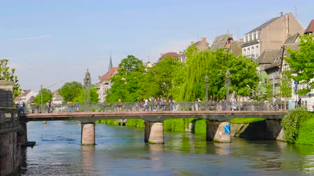 half timbered houses : Strasbourg, France - Circa 2019: Strasbourg famous Bridge Pont Ste Madeleine and pedestrian street Quai des Bateliers with half timbered houses and people having fun resting on the Ill border on a warm spring day Stock Footage