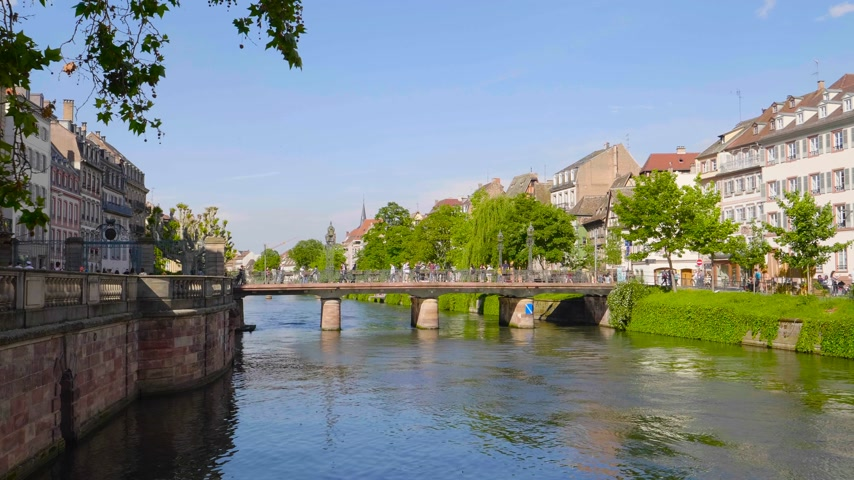 half timbered : Strasbourg, France - Circa 2019: Strasbourg famous Bridge Pont Ste Madeleine and pedestrian street Quai des Bateliers with half timbered houses and people having fun resting on the Ill border on a warm spring day Stock Footage