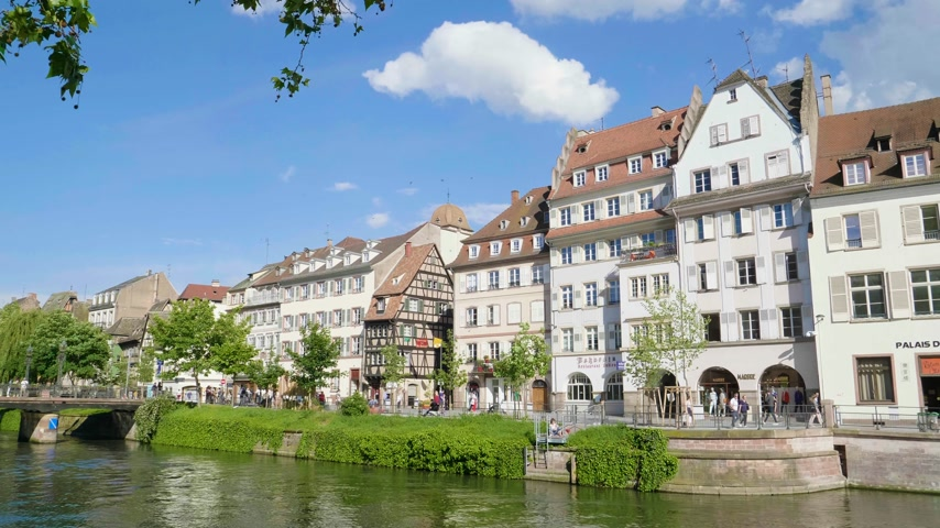 half timbered houses : Strasbourg, France - Circa 2019: Side view of Strasbourg famous promenade pedestrian street Quai des Bateliers with half timbered houses and people having fun resting on the Ill border on a warm spring day