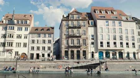 half timbered houses : Strasbourg, France - Circa 2019: Time lapse fast motion Strasbourg famous promenade pedestrian street Quai des Bateliers with half timbered houses and Ill river border on a warm spring day Stock Footage