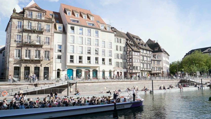 half timbered : Strasbourg, France - Circa 2019: Strasbourg famous promenade pedestrian street Quai des Bateliers with half timbered houses and people having fun resting on the Ill border on a warm spring day and Batorama boat