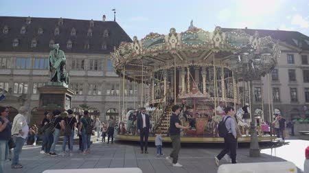 пони : Strasbourg, France - Circa 2019: People kids adults having fun taking photos at the merry go round in central Strasbourg Place Gutenberg