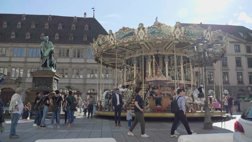 poník : Strasbourg, France - Circa 2019: People kids adults having fun taking photos at the merry go round in central Strasbourg Place Gutenberg