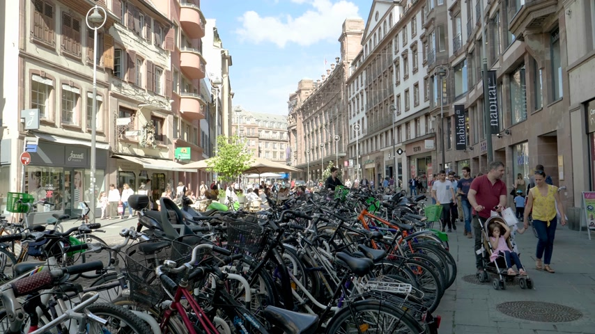 choise : Strasbourg, France - Circa 2019: Large parking on the city center street for bicycles in central Strasbourg with pedestrians calmly walking and Galeries Lafayette building in background  Rue du Vingt-Deux Novembre