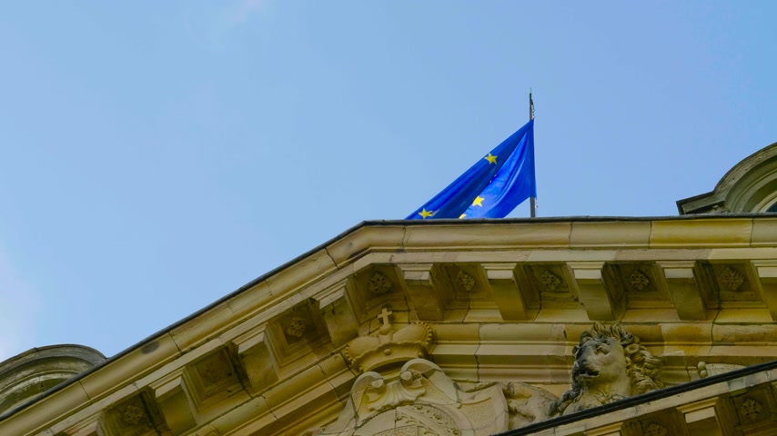 baixo ângulo : Low angle view of EU European Union flag official symbol of two separate international organizations, the Council of Europe CoE and the European Union EU on top of building Stock Footage
