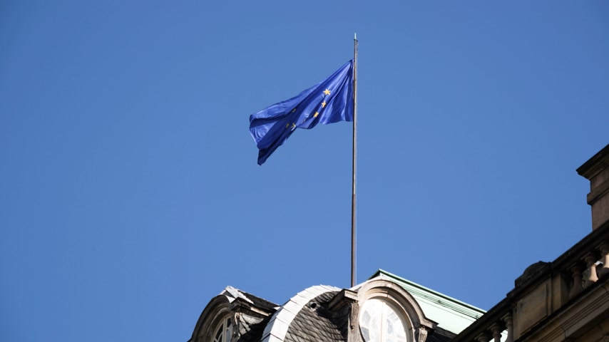 baixo ângulo : Low angle view of EU European Union official flag waving on the roof of Palais Rohan Palace in Strasbourg, Alsace, France Stock Footage