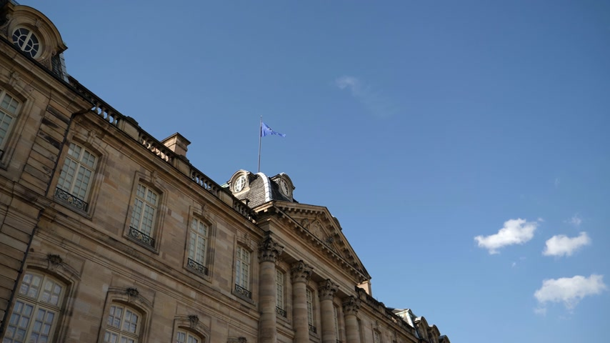 baixo ângulo : Low angle view of slow motion waving EU flag on top of Palais Rohan Strasbourg, France