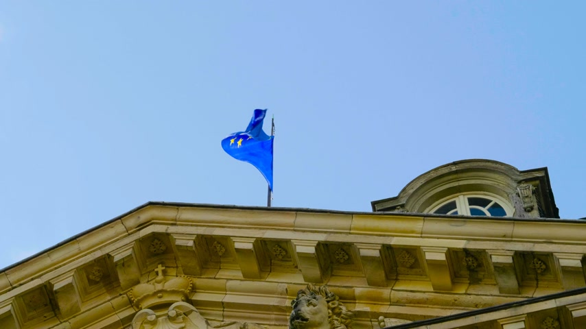 baixo ângulo : Slow motion low angle view of EU European Union official symbol of two separate international organizations, the Council of Europe CoE and the European Union EU waving on top of Palais Rohan Strasbourg