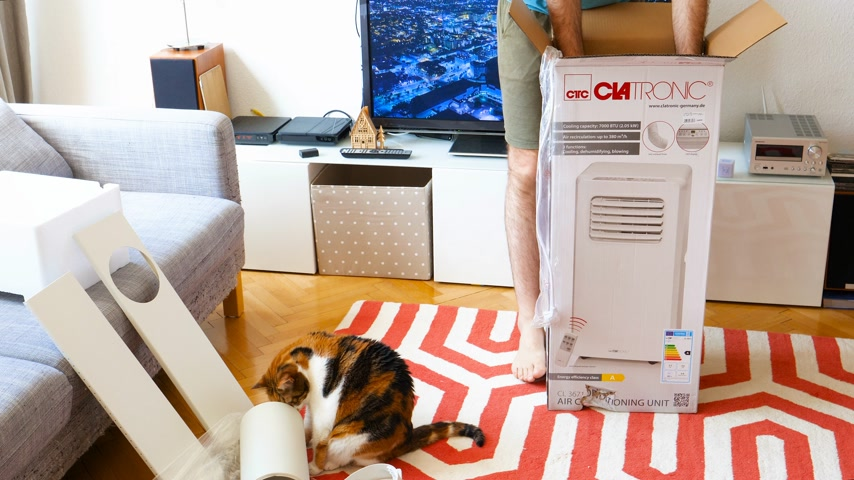 termostat : Paris, France - Circa 2019: Young man being helped by his cat unboxing installing new portable air conditioner unit AC during hot summer in his living room getting the device from his box Wideo