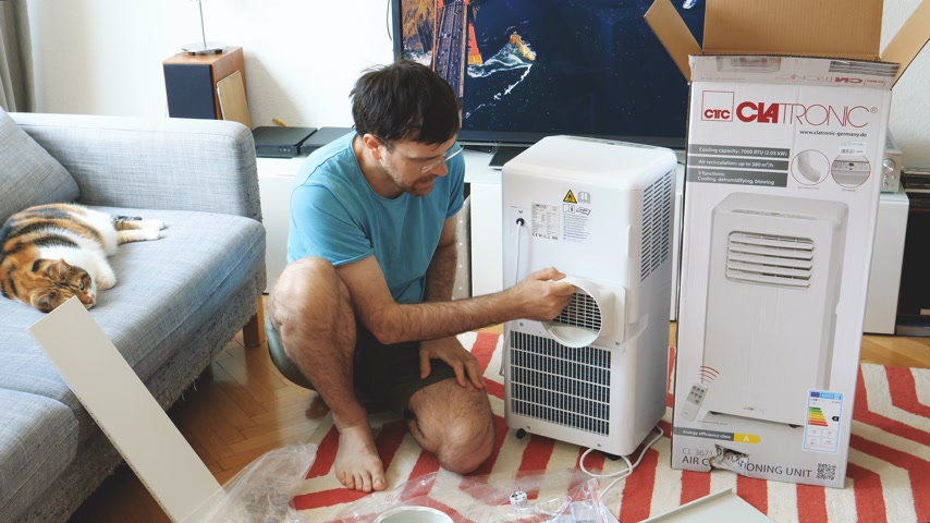 compressor : Paris, France - Circa 2019: Young man being helped by his cat unboxing installing new portable air conditioner unit AC during hot summer in his living room - assembling vent tube - Clatronic CL 3671 Stock Footage