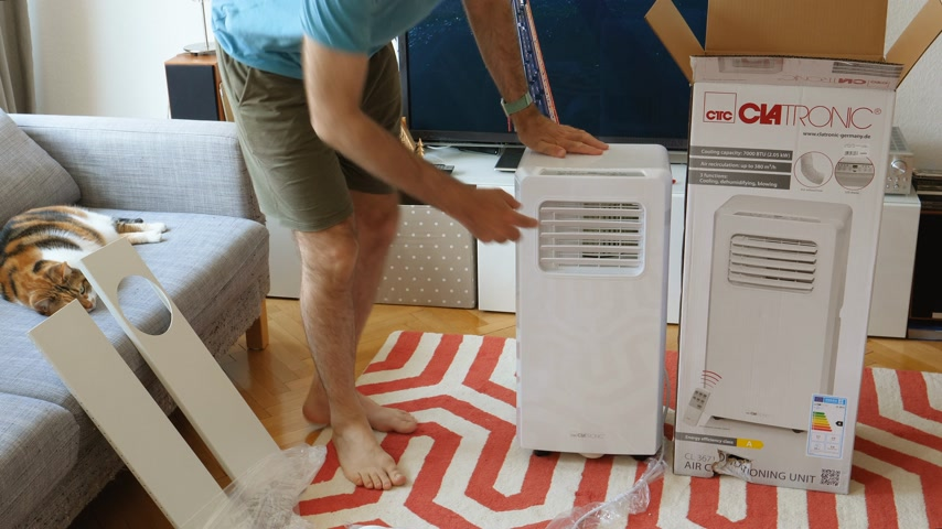 kondenzátor : Paris, France - Circa 2019 Young man being helped by his cat unboxing installing new portable air conditioner unit AC during hot summer in his living room inspecting the device and all the accessories